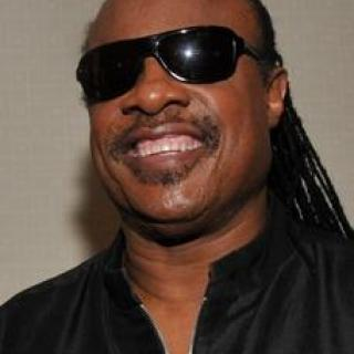Smiling black man with big sunglasses and long braids in a black shirt