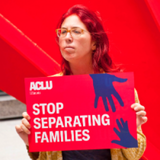 Woman with glasses and long red hair outside holding a sign that says Stop Separating Families