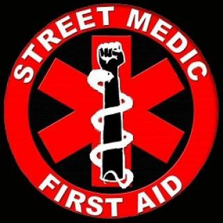 Red circle with star shape in middle with fist and snake, words Street Medic First Aid