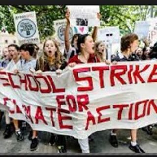 Young people marching outside with a banner reading School Strike for Climate Action