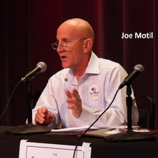 White man with glasses and a white shirt talking into a mic at a table making a hand gesture with the words Joe Motil