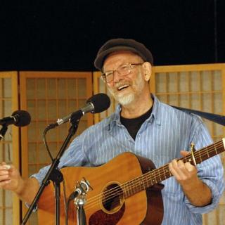 Man with gray goatee and black cap holding guitar at microphone smiling