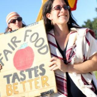 White women with long dark hair and sunglasses holding sun that says Fair Food Taste Better