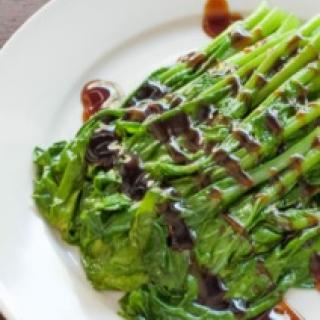 Asparagus on a plate with a brown drizzle across it