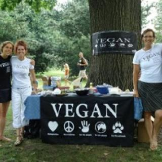 Three happy people by a table outside that says VEGAN on a sign