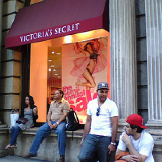 People sitting on a ledge outside a Victoria's Secret store