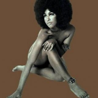 Sixties-looking photo of naked black woman covering up her private parts with arms and legs, she has a huge Afro against a brown background