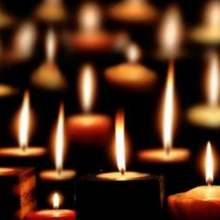 Lots of lit candles glowing in the darkness