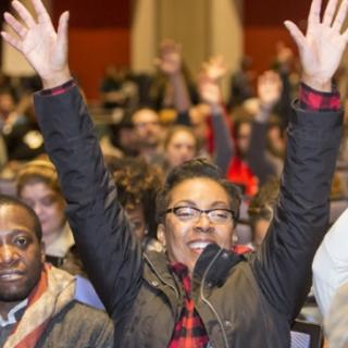 Black woman with glasses in front of a huge crowd of people smiling with both hands held high above her head