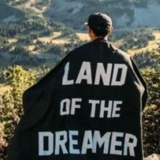 Man standing on a hill looking out with his back to the camera with a cape on with the words Land of the Dreamer