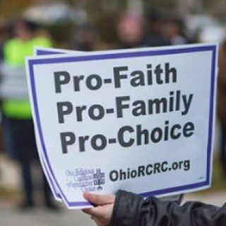 Hand holding a sign that says Pro Faith, pro-family, pro-choice