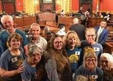 Lots of smiling white people male and female leaning toward each other all wearing blue T-shirts in a city council chambers