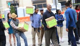 Many people holding boxes