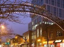 Lighted metal arch over street next to tall building