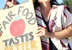 White women with long dark hair and sunglasses holding sun that says Fair Food Taste Better