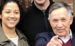 Young black woman smiling on the left, tall white man smiling in the middle and older white man pointing at the camera standing in front of a brick wall
